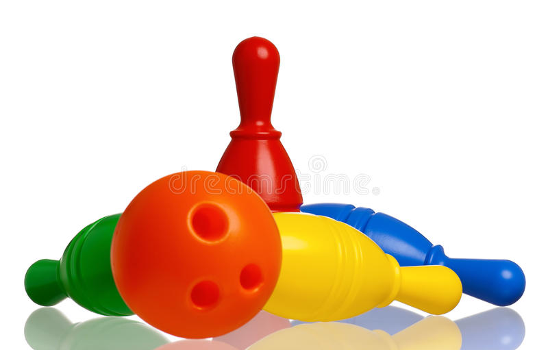 Toy bowling. Colorful plastic skittles of toy bowling with orange ball isolated on a white background royalty free stock photos