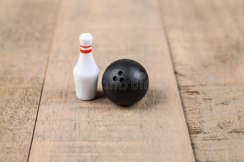 Toy bowling ball and pins. Isolated on a wood background royalty free stock photo