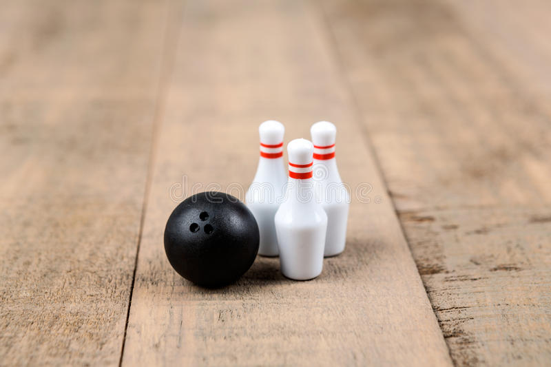 Toy bowling ball and pins. Isolated on a wood background stock image