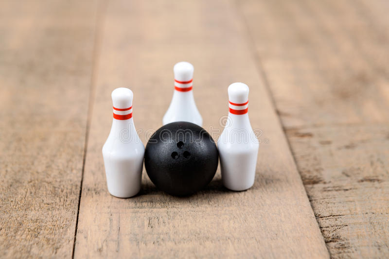 Toy bowling ball and pins. Isolated on a wood background stock photos