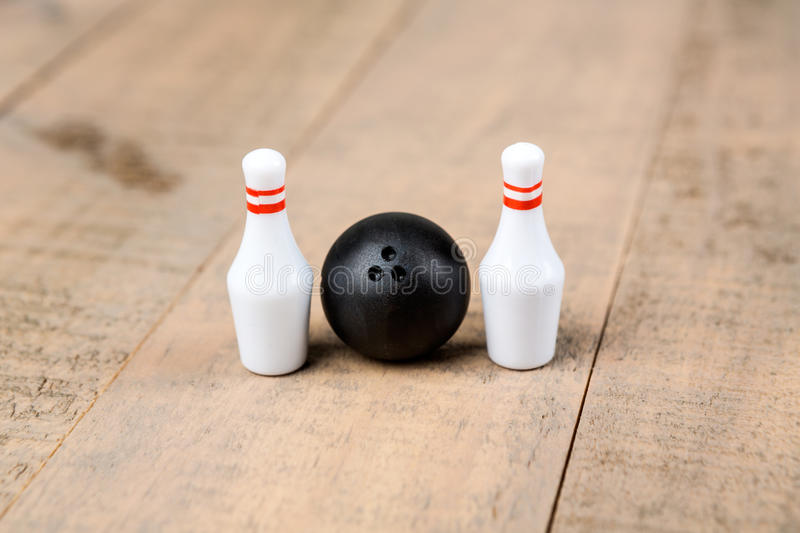 Toy bowling ball and pins. Isolated on a wood background stock images