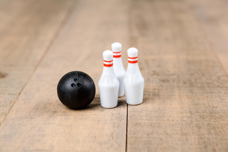 Toy bowling ball and pins. On a wood background stock photography