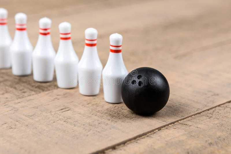 Toy bowling ball and pins. On a wood background royalty free stock photos