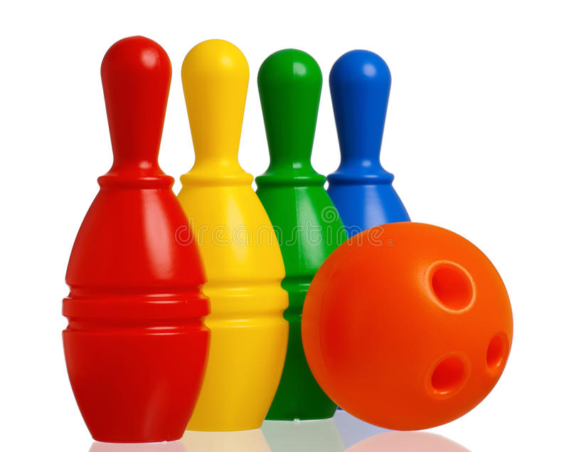 Toy bowling. Colorful plastic skittles of toy bowling with orange ball on a white background stock images