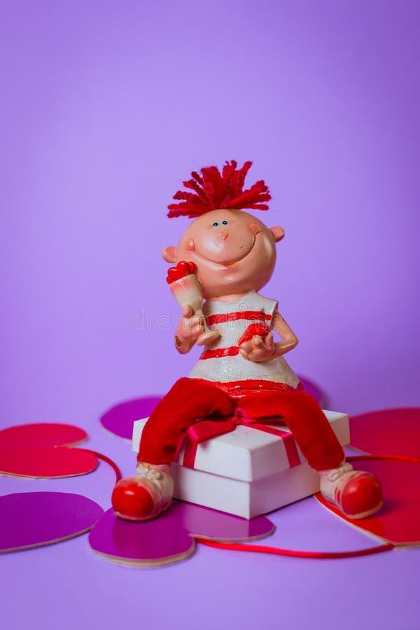 Toy Boys senta-se em uma caixa de presente branca com uma fita vermelha nos corações de papel em um fundo roxo foto de stock
