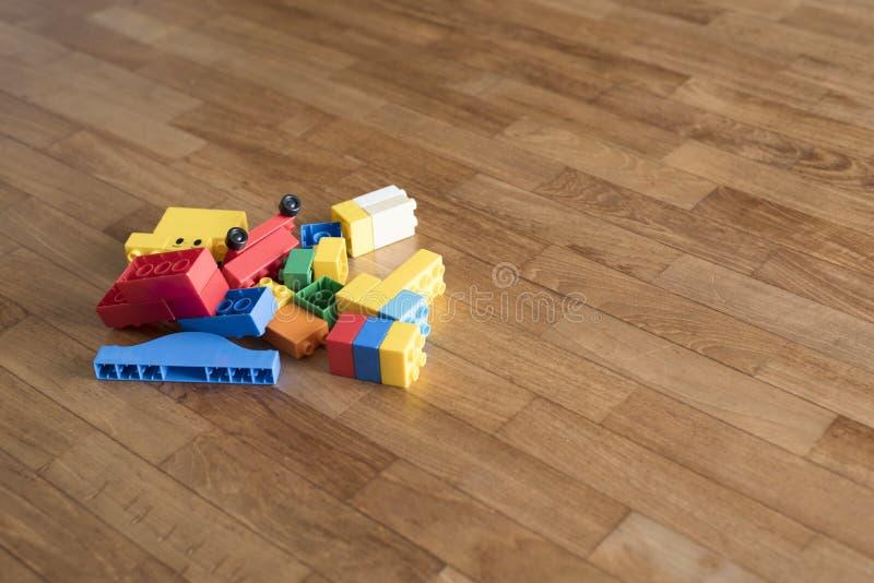 Toy bricks on wooden floor. Colorful plastic blocks. royalty free stock image