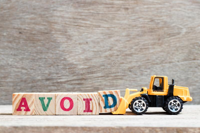 Toy bulldozer hold block d to complete word avoid on wood background. Toy bulldozer hold letter block d to complete word avoid on wood background royalty free stock photo