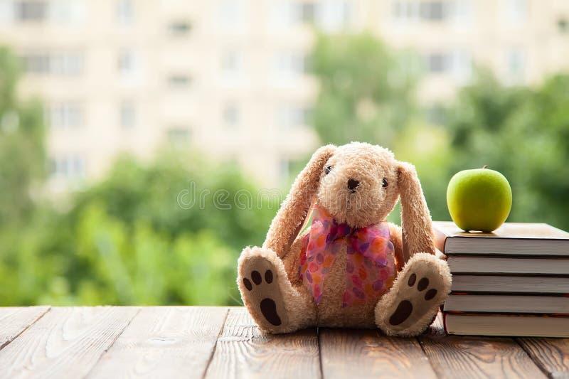 Toy Bunny que sentam-se para trás, mentira ao lado de uma pilha de livros e Apple verde Conceito em antecipação ao ano escolar no imagem de stock royalty free