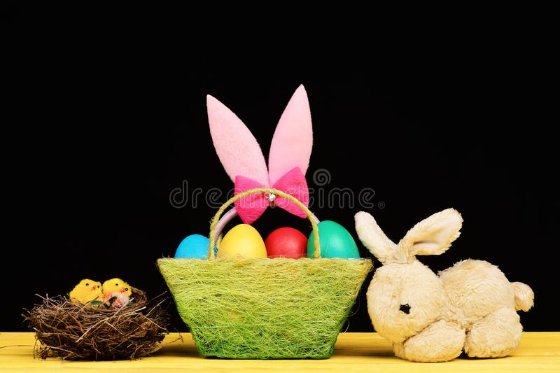 Toy bunny on wooden table by Easter egg in nest stock images