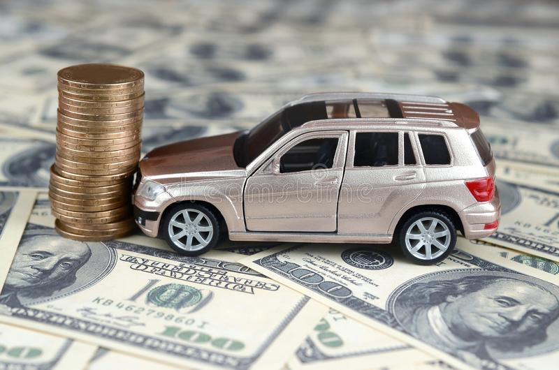 Toy car in accident on a background of 100 dollar bills and stack of golden coins stock photos