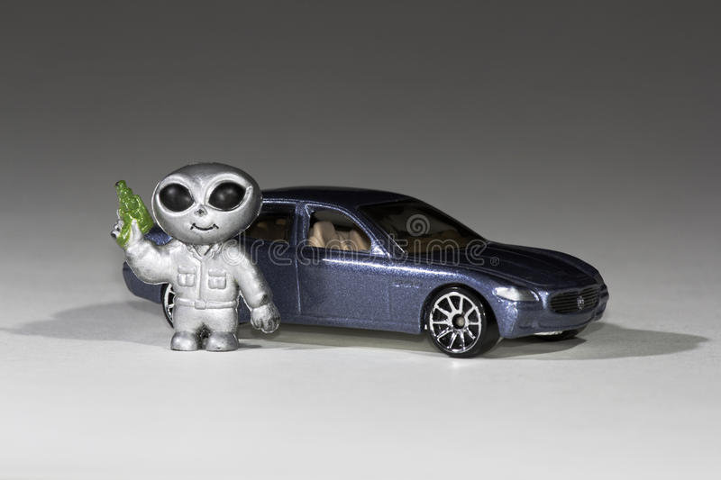 Toy car alien. Alien with pistol standing by toy car stock photo
