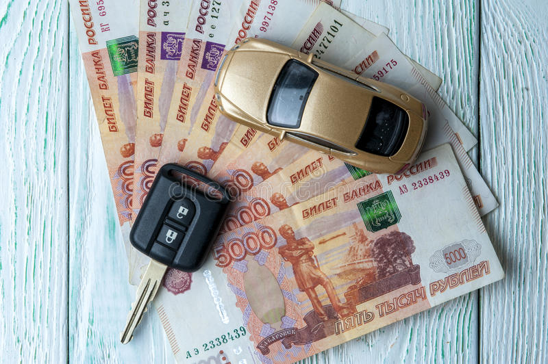 Toy car, banknotes and car key. Golden toy car, banknotes of russian rubles and car's key on wooden background. Financial theme. Horizontal view royalty free stock images