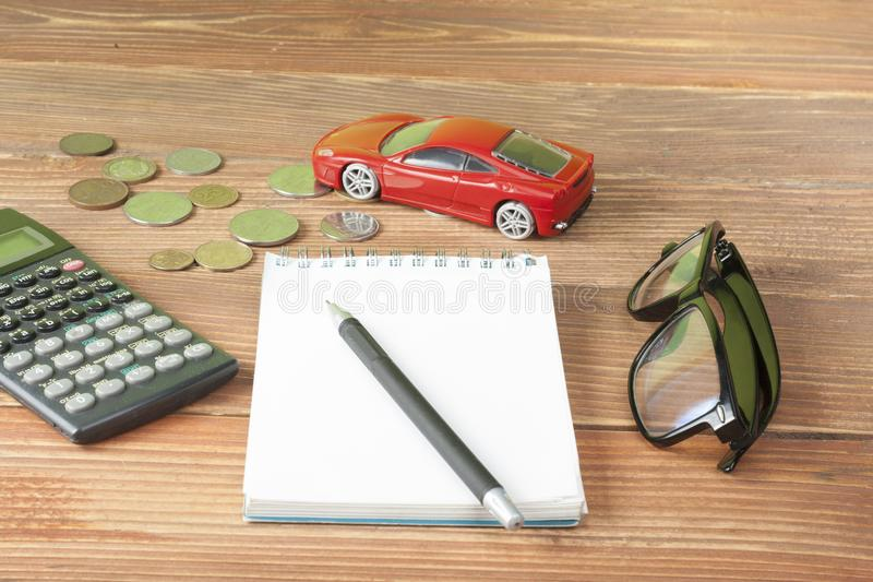 Toy car,calculator and coins. Loan, insurance and savings concept. Toy car,calculator and coins on wooden table.. Loan,insurance and saving concept stock images