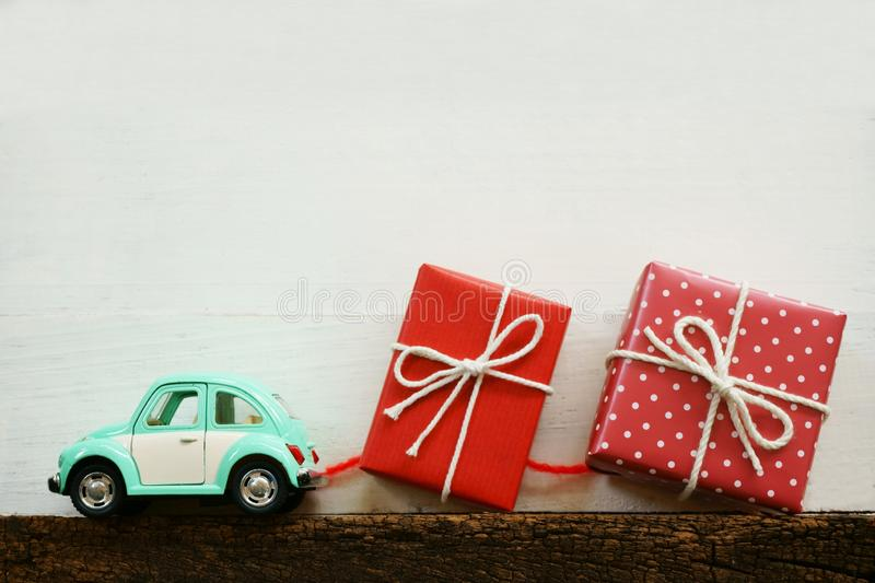 Toy car carrying red lovely gift box on white background, sweet valentine present delivery concept. Copy space stock photography
