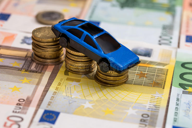 Toy car on coin and euro bills. Blue toy car on coin and euro bills stock photo