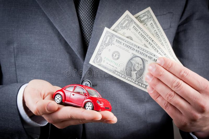 Toy car and dollars in the hands of business man concept for insurance, buying, renting, fuel or service and repair costs. Toy car and dollars in the hands of royalty free stock image