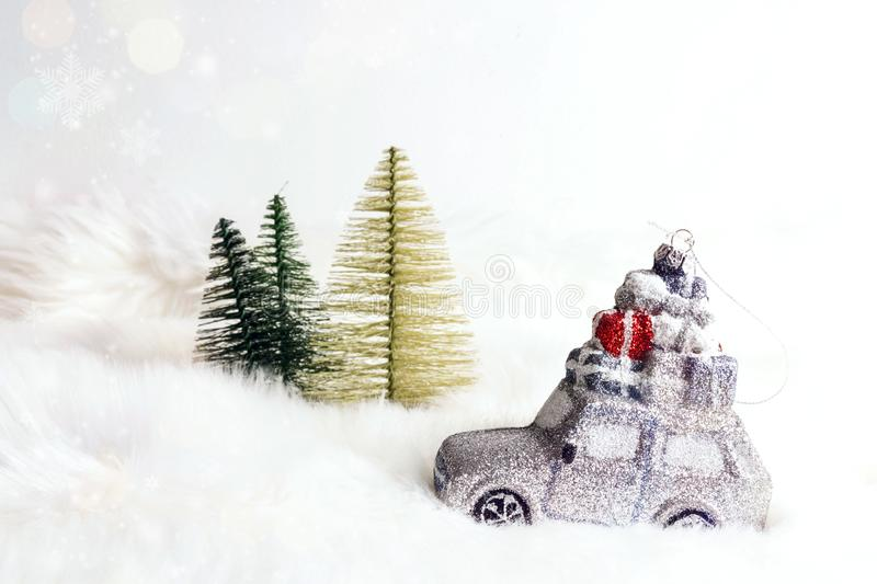 Toy car with gifts and fir trees on white fur background that looks like snow. Christmas and New year holiday celebration concept. Copy space stock images