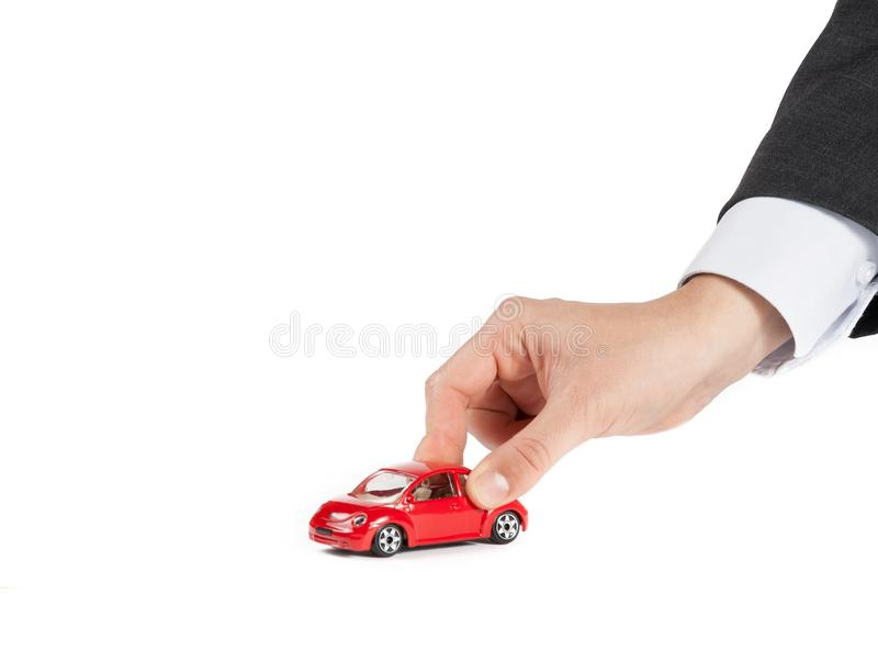 Toy car and hand of man, concept for insurance, buying, renting, fuel or service and repair costs. On white background royalty free stock image