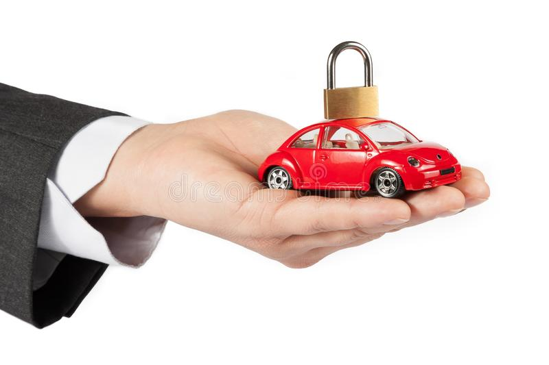 Toy car with lock on top in the hand of business man concept for insurance, buying, renting, fuel or service and repair costs. Toy car with lock on top in the stock photo