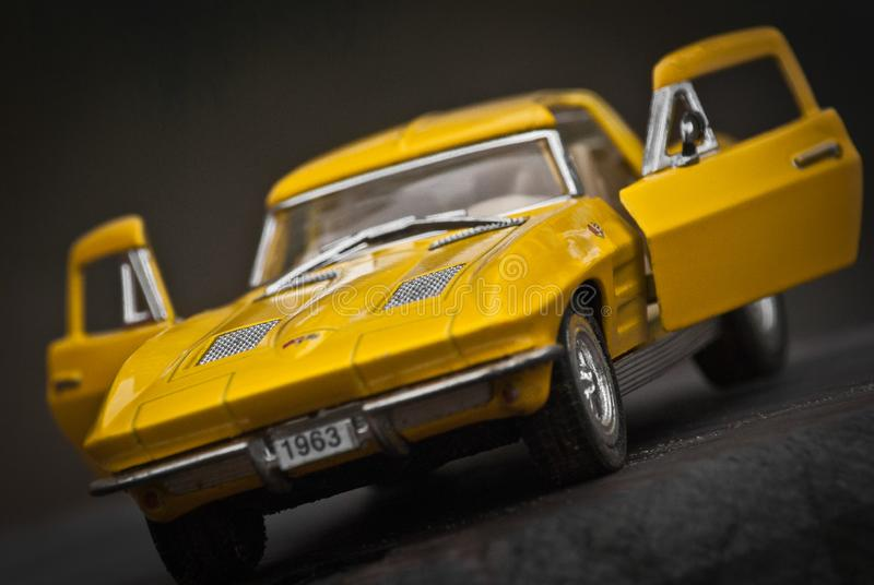 Toy car model Corvette Sting Ray 1963 year. Yellow color. Front view. Open doors. Close-up. Macro.  stock photography