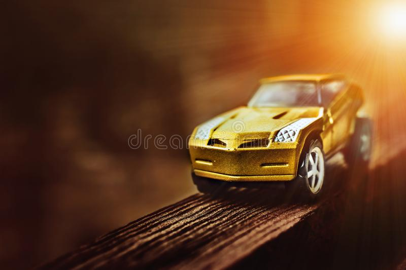 Toy car model. On the open air goes by wooden road with backlit sunlight. Horizontal view, copy-space royalty free stock photography