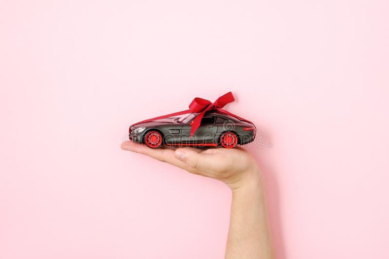 Toy car model with ribbon bow on human hand on pink background. Auto dealership and rental concept.  royalty free stock images