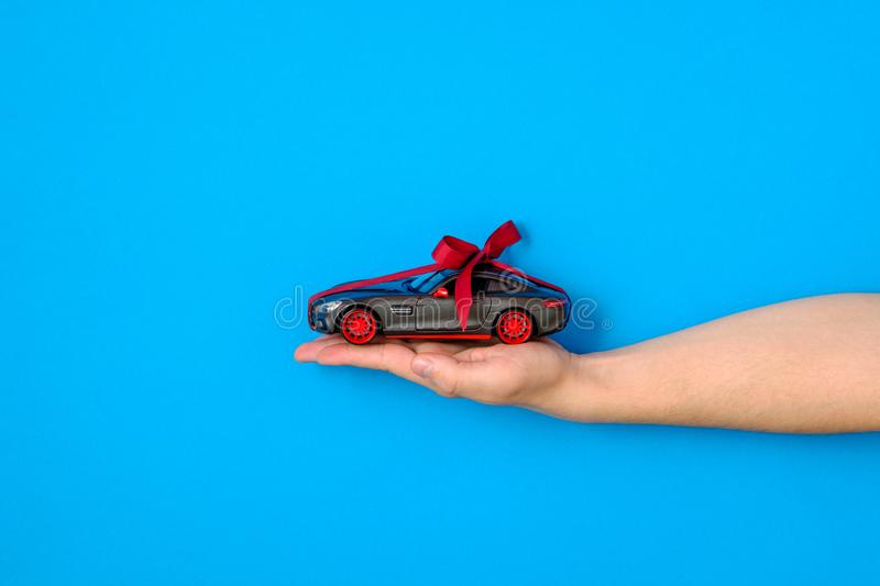Toy car model tied with a red ribbon and bow on human hand on blue background. Auto dealership and rental, buy new auto, car as. Gift or present, draw car royalty free stock image