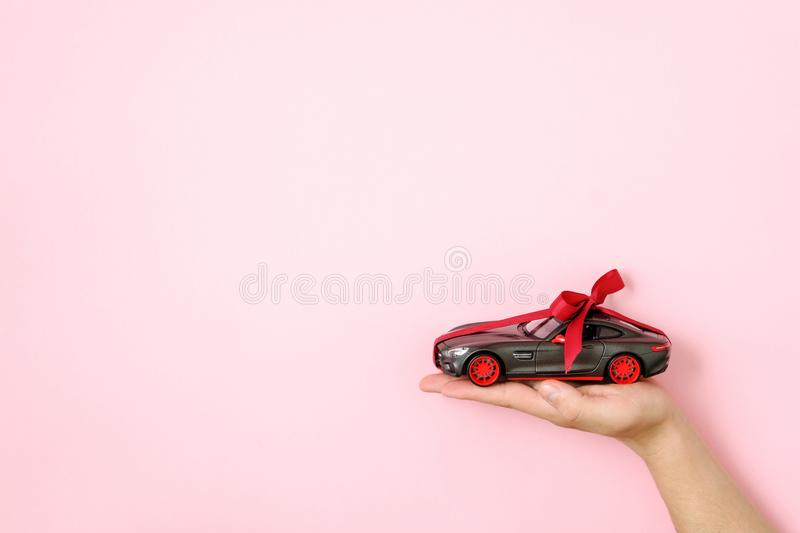 Toy car model tied with a red ribbon and bow on human hand on pink background. Auto dealership and rental, car as gift or present. Draw car, chance to win royalty free stock images