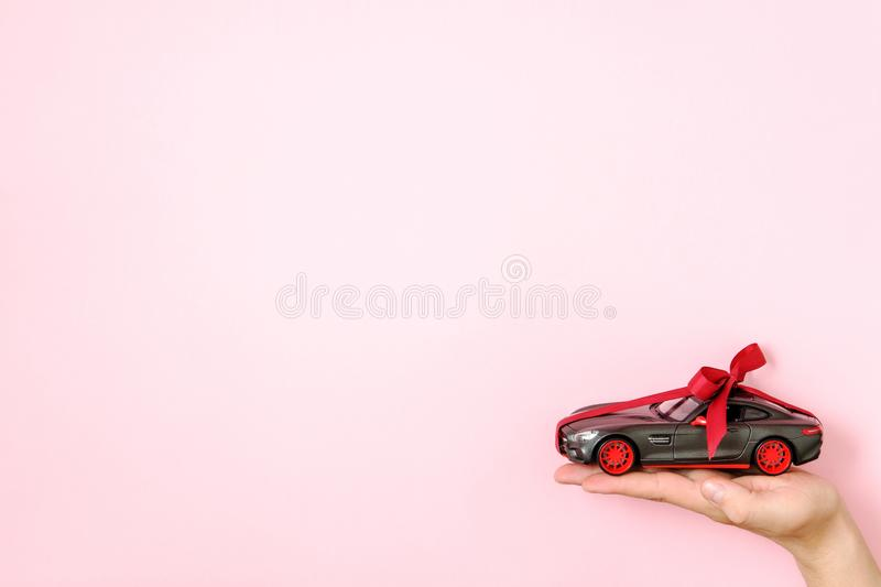 Toy car model tied with a red ribbon and bow on human hand on pink background. Auto dealership and rental, car as gift or present. Draw car, chance to win royalty free stock photo