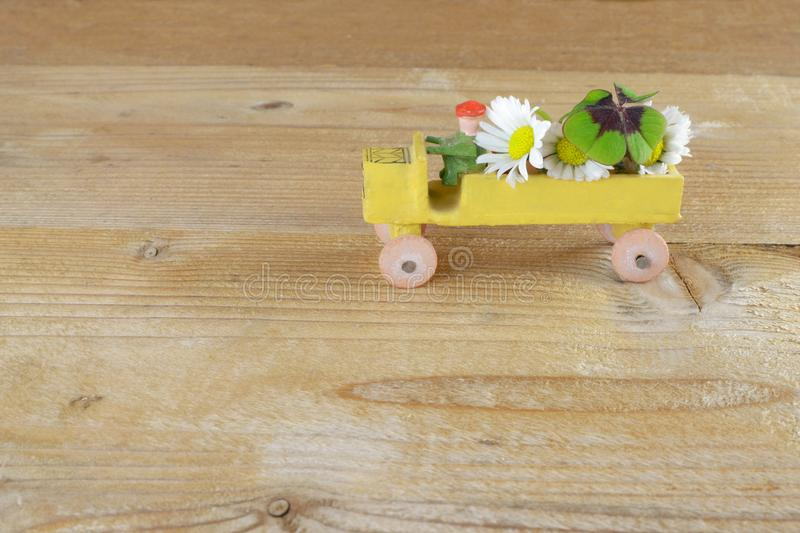 A toy car with a nice flower bouquet and a cloverleaf. An old wooden toy car with daisy and cloverleaf for good luck. Yellow truck on a wooden background. Space royalty free stock image