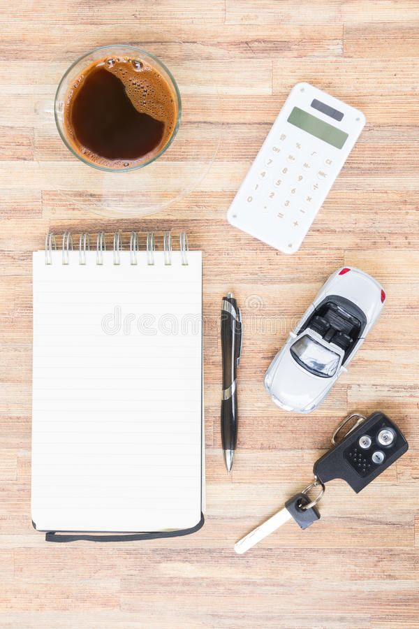 Toy car with notebook, calculator and coffee. On wooden table stock photo