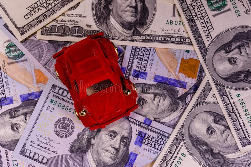 Toy car on a one hundred dollar bills. Toy car on one hundred dollar bills royalty free stock photos