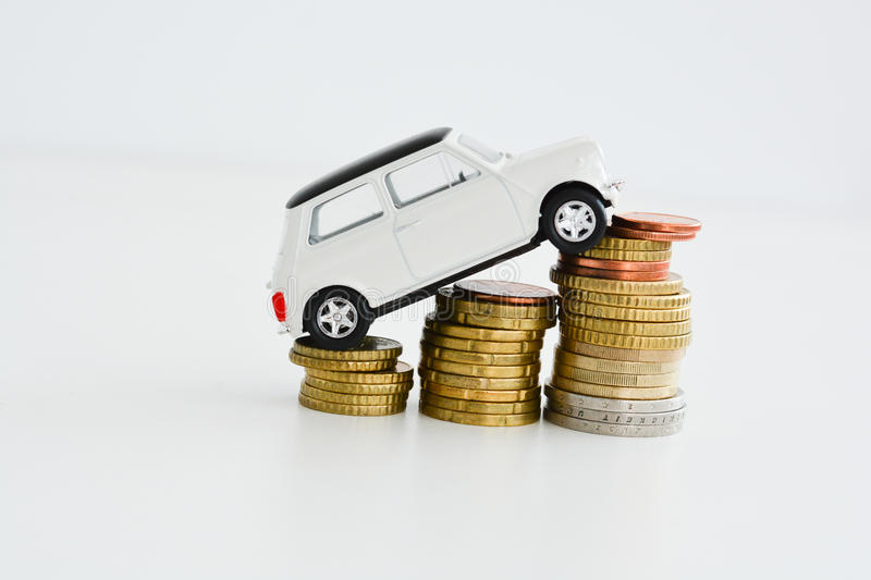 Toy car over a stack of coins. Suggesting the rise of prices stock images