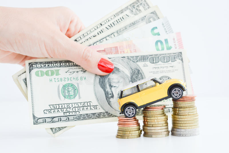Toy car over a stack of coins. Suggesting the rise of prices royalty free stock photo