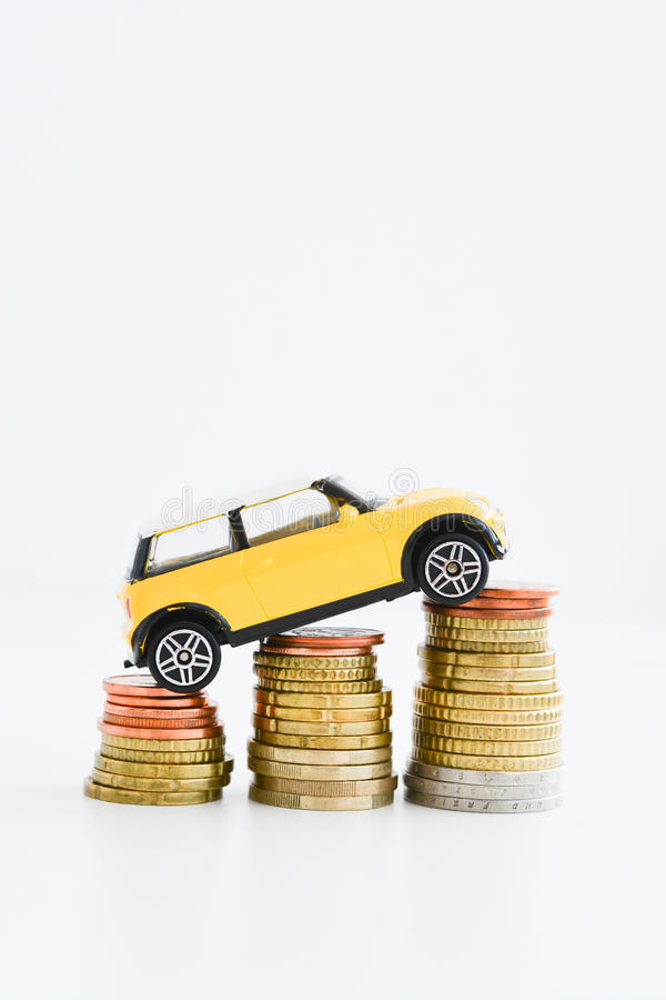 Toy car over a stack of coins. Suggesting the rise of prices royalty free stock images