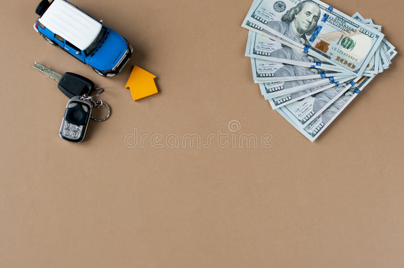 Toy car, toy house, keys with remote control alarm and money. Flat lay toy car, toy house, keys with remote control alarm and money on the table stock photos