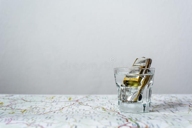 Toy car in vodka shot on a road map. royalty free stock images