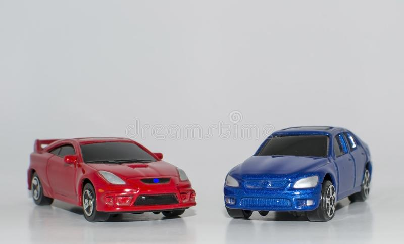 Toy Cars Red and Blue Color on White Background. Real life models in from Toy Cars of Red and Blue Color on White Background standing side by side showing bonnet stock photos