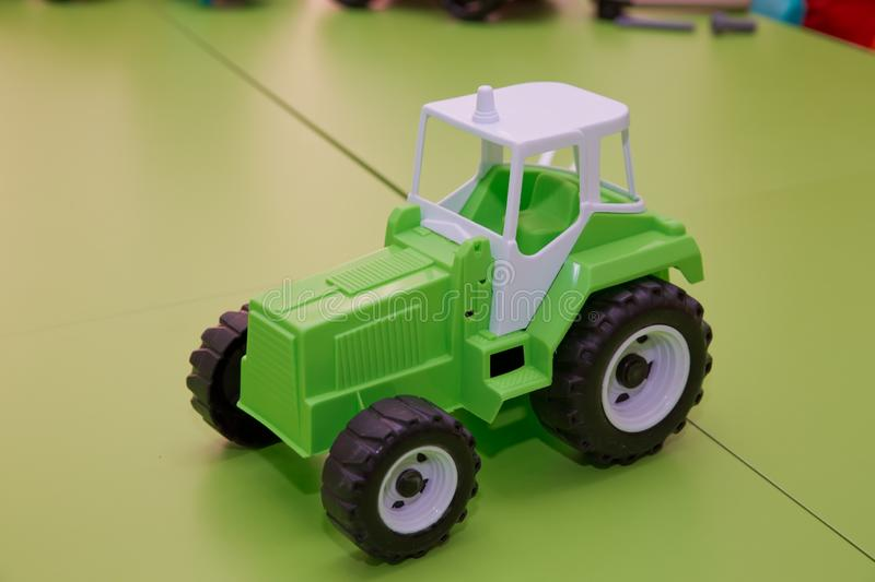 Toy for children. Toy tractor on green background . Green Tractor royalty free stock photo