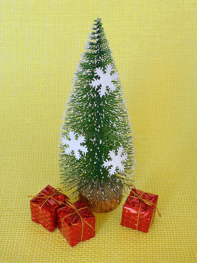 Toy Christmas gifts near a toy Christmas tree with white snowflakes are on a yellow textural background. Close up royalty free stock images