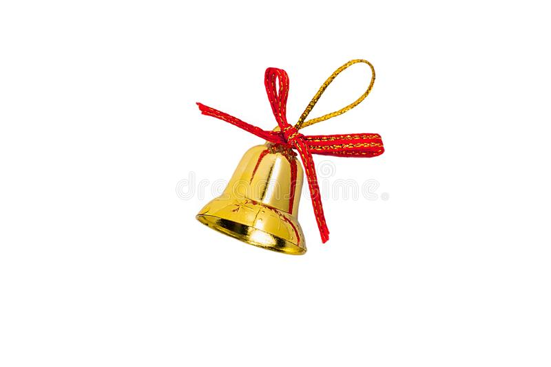 Toy for the Christmas tree branches in the form of a golden bell with a red satin bow and a loop of shiny thread for hanging royalty free stock photo