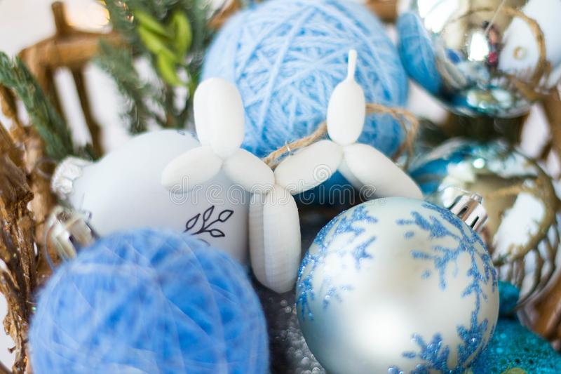 Toy for the Christmas tree in the form of a dog lies on a background of blue Christmas balls. 3d toys. 2020. toy for the Christmas tree in the form of a dog lies stock images