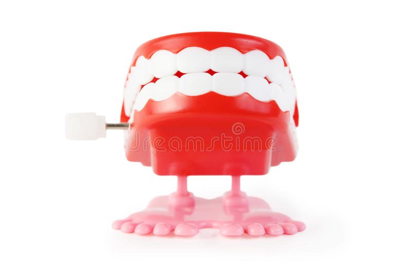 Toy clockwork jaw with white teeth on pink legs. Bright toy clockwork jaw with white teeth on pink legs on white background royalty free stock photography