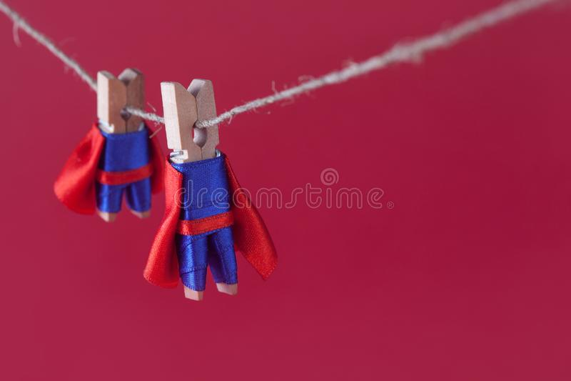 Toy clothespin peg superheroes on rope clothesline. Big small super team characters red background. soft focus. macro. View, shallow depth of field royalty free stock photo