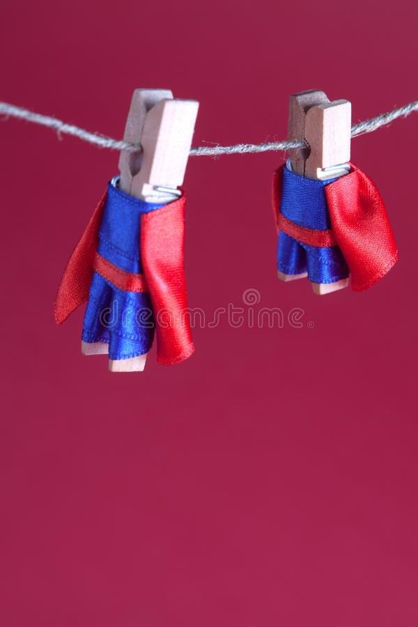 Toy clothespin peg superheroes on rope clothesline. Big small super team characters red background. soft focus. macro. View, shallow depth of field stock photo