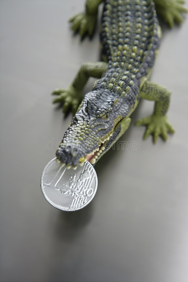 Toy cocodrile, aligator with one euro coin in jaws royalty free stock images