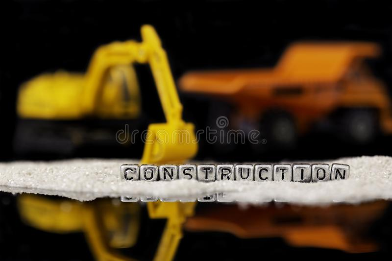 Toy construction vehicles and sand with the word construction on beads stock photos