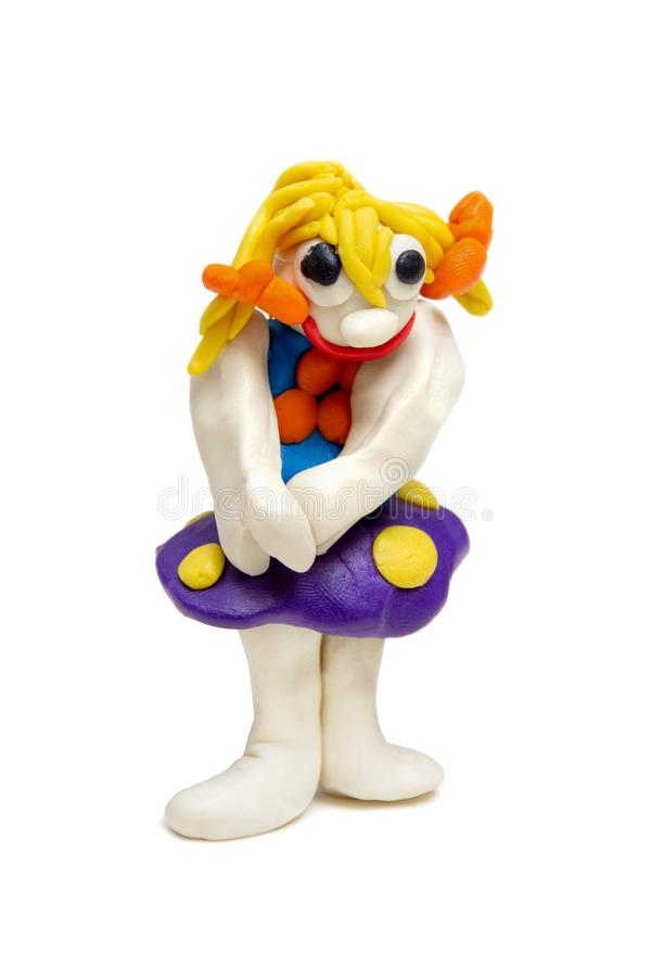 Toy craft from plasticine. plasticine funny girl with yellow hair and blue skirt royalty free stock photos