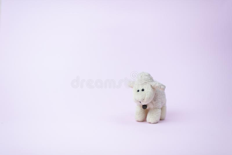 Toy of a cute little white sheep with a bell on a pink background stock photos