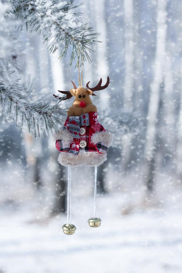 Toy deer with bells, Christmas decoration, close-up, against the winter forest, where snow falls. Color red white blue green christmas decor royalty free stock images